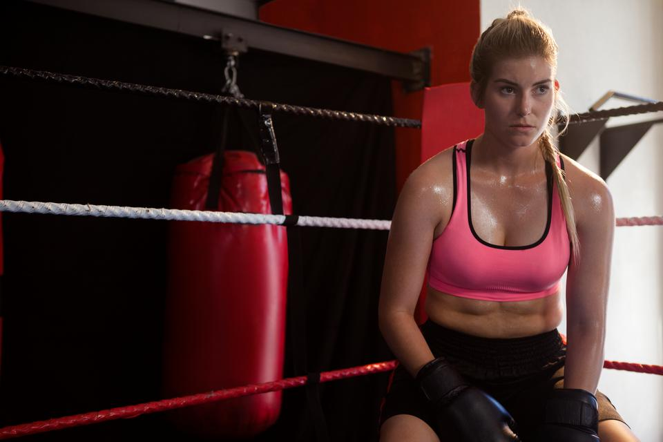 """Thoughtful woman sitting in boxing ring"" stock image"