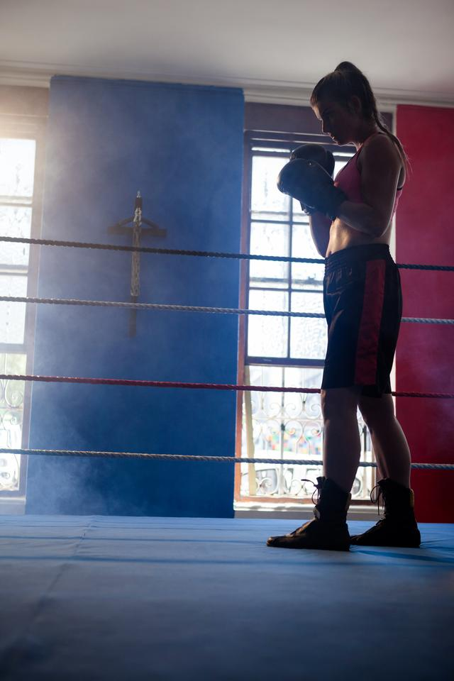 """Determined woman standing in boxing ring"" stock image"