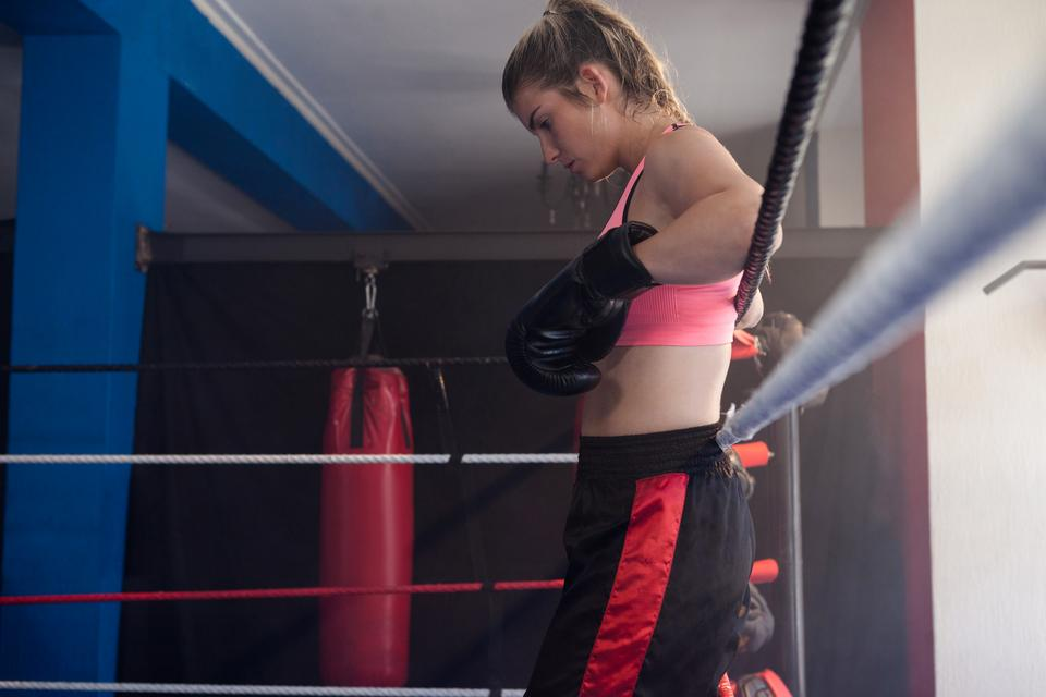 """Thoughtful woman standing in boxing ring"" stock image"