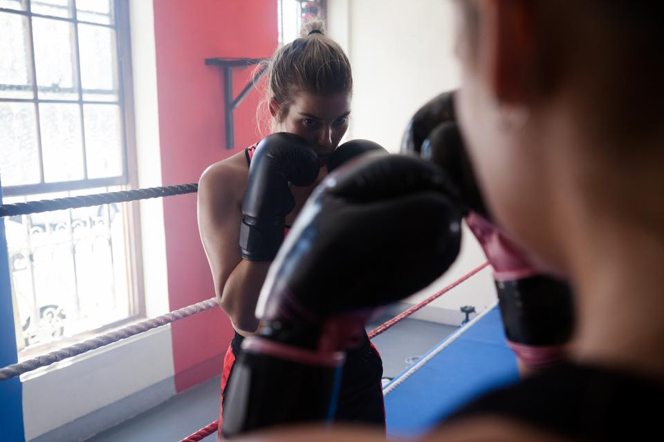 """Trainer assisting woman in boxing"" stock image"