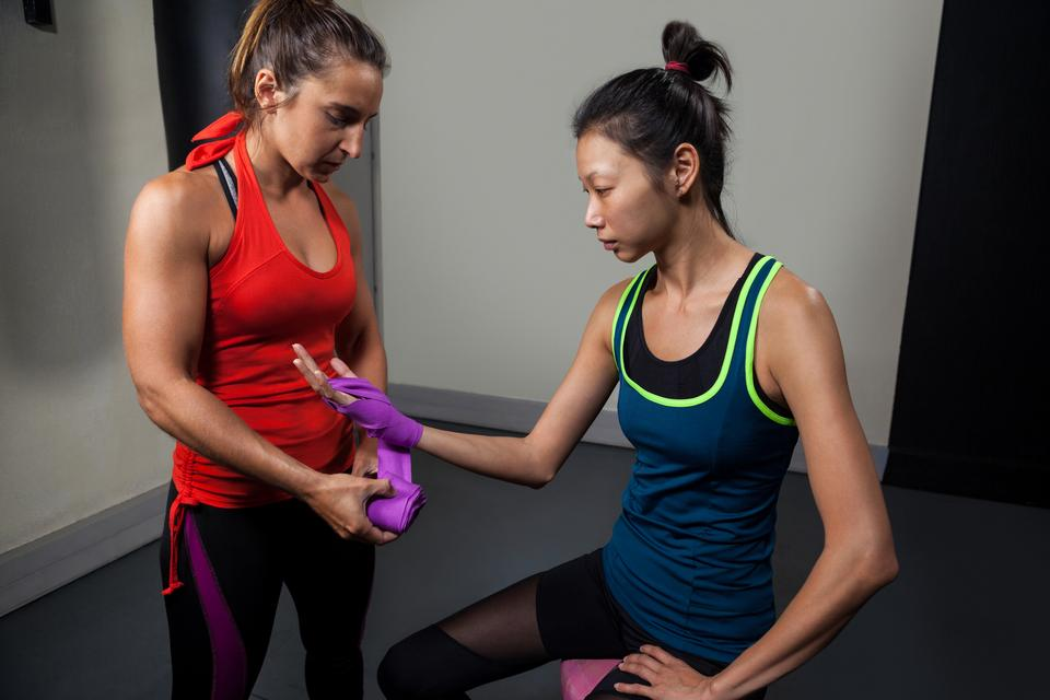 """""""Trainer tying hand wrap on woman hand"""" stock image"""