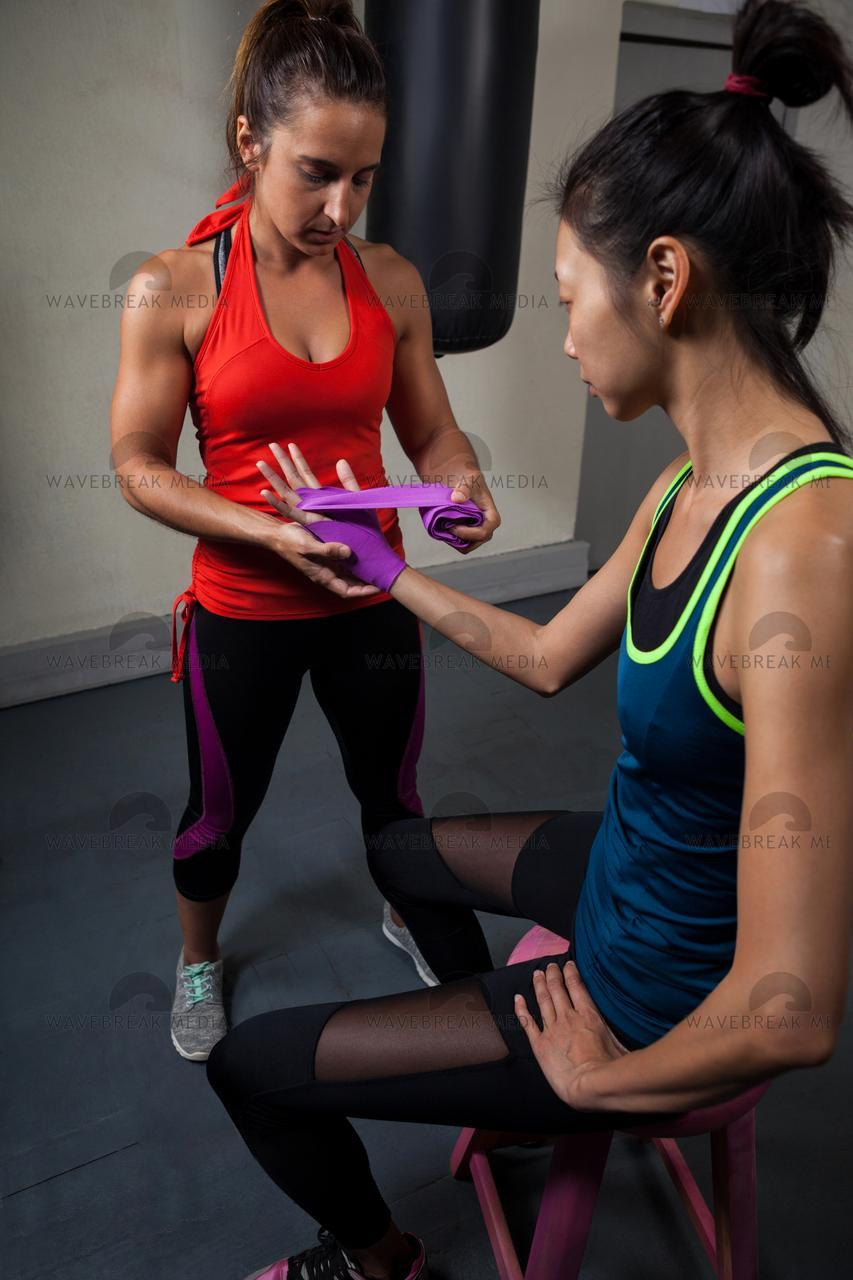 """Trainer tying hand wrap on woman hand"" stock image"