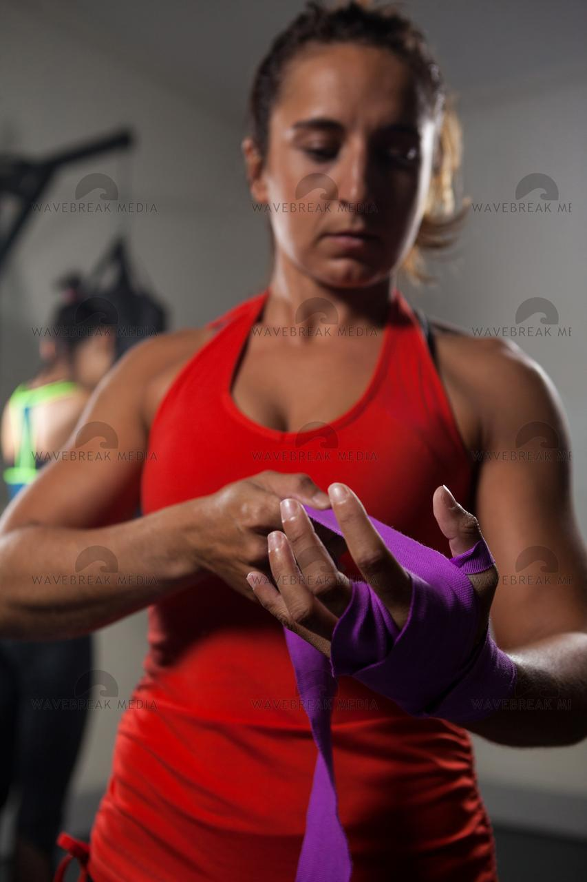 """Woman tying hand wrap on hand"" stock image"