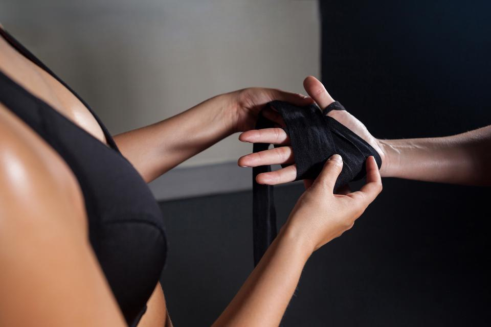 """""""Trainer trying hand wrap on womans hand"""" stock image"""