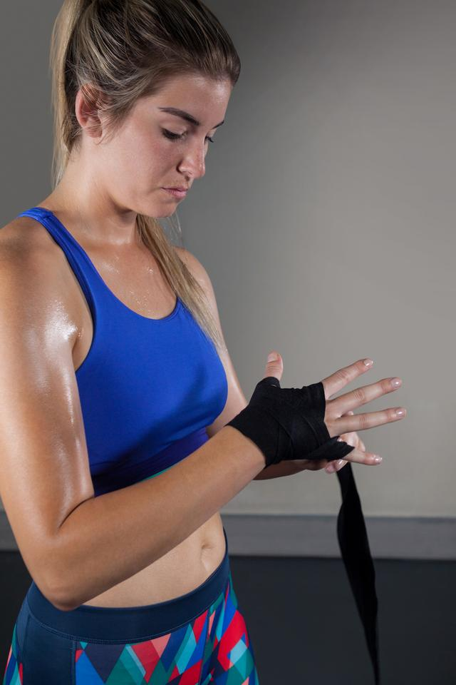 """Woman tying hand wrap on hand in fitness studio"" stock image"