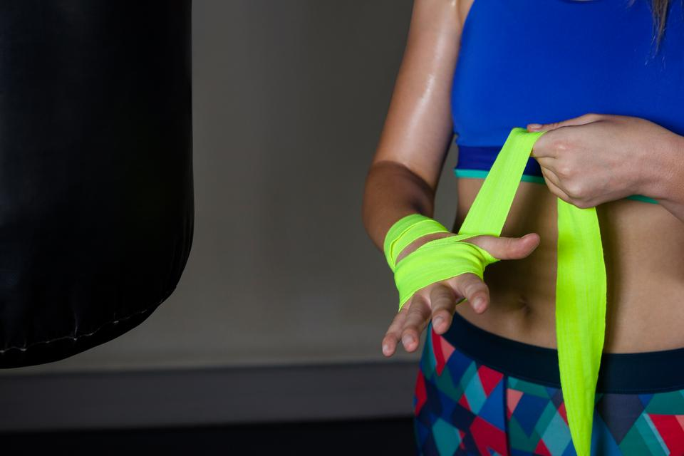 """""""Woman tying hand wrap on hand in fitness studio"""" stock image"""