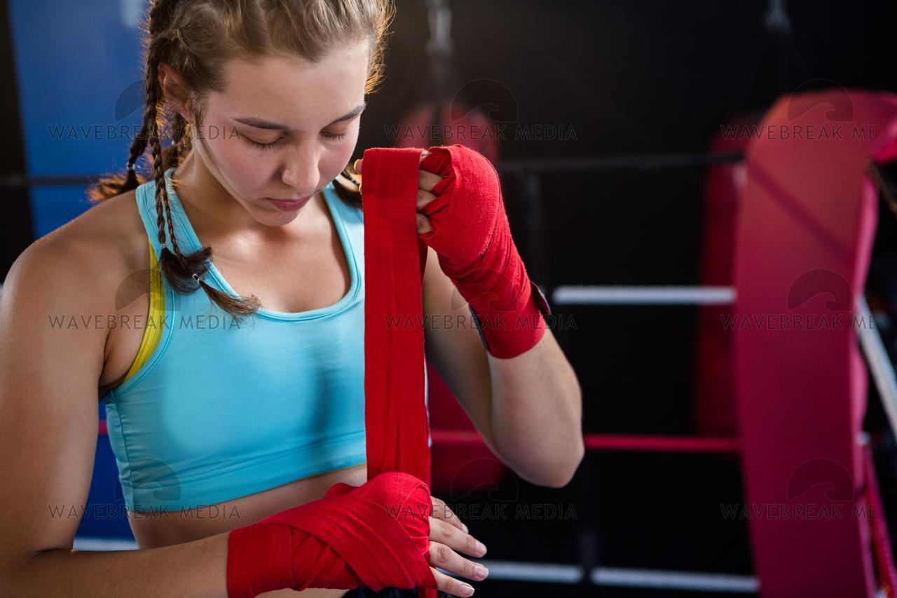 """Young female athlete wrapping red bandage on hand"" stock image"