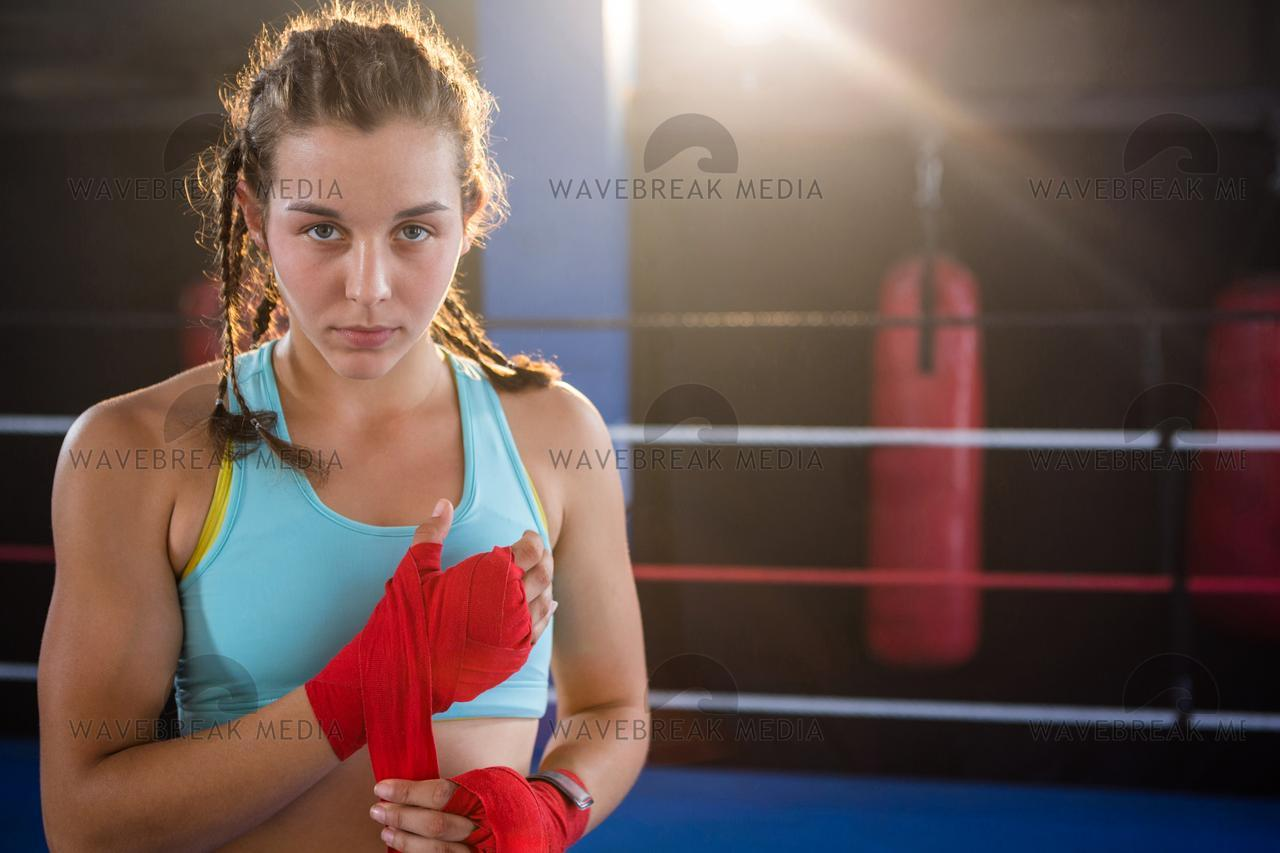 """Portrait of young female athlete wrapping red bandage on hand"" stock image"