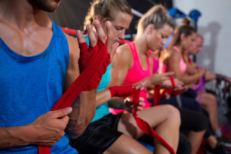 """Row of athletes wrapping bandages on hands"" stock image"
