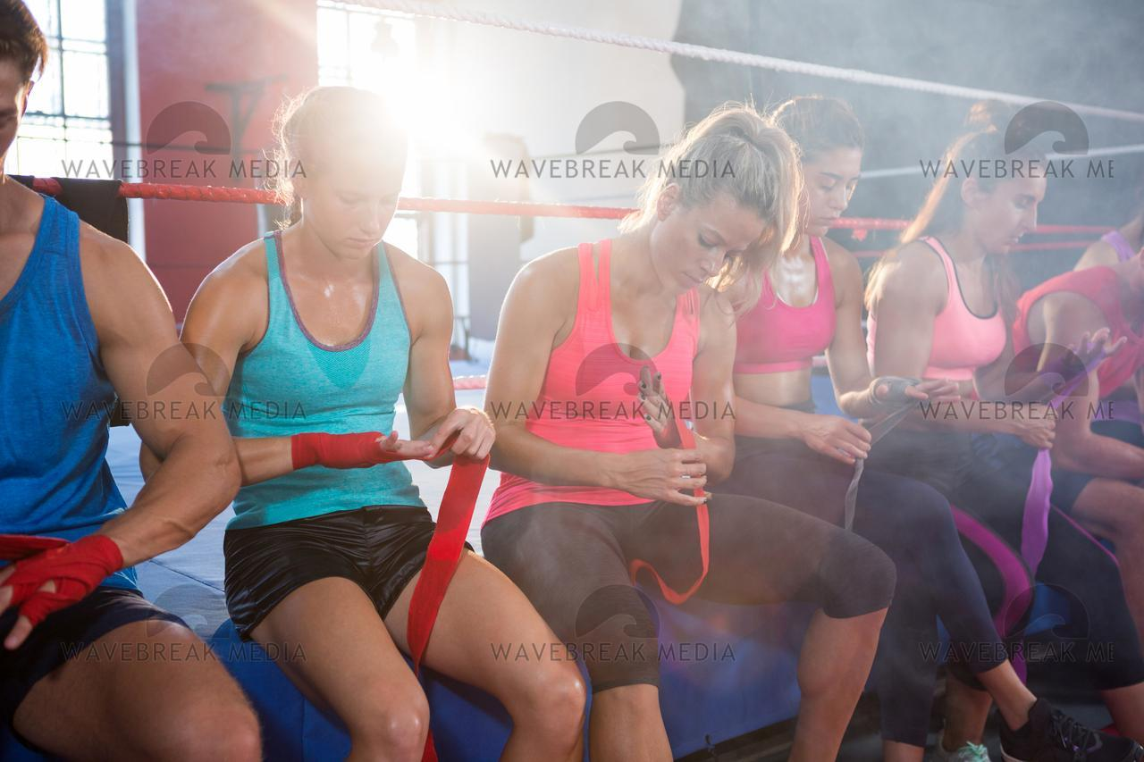 """Back lit athletes sitting on boxing ring while wrapping bandages"" stock image"
