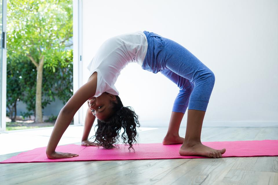 """Portrait of girl bending over backwards while exercising"" stock image"