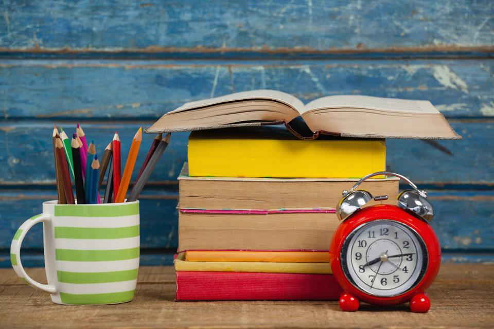 """""""Stack of books, alarm clock and pen holder"""" stock image"""