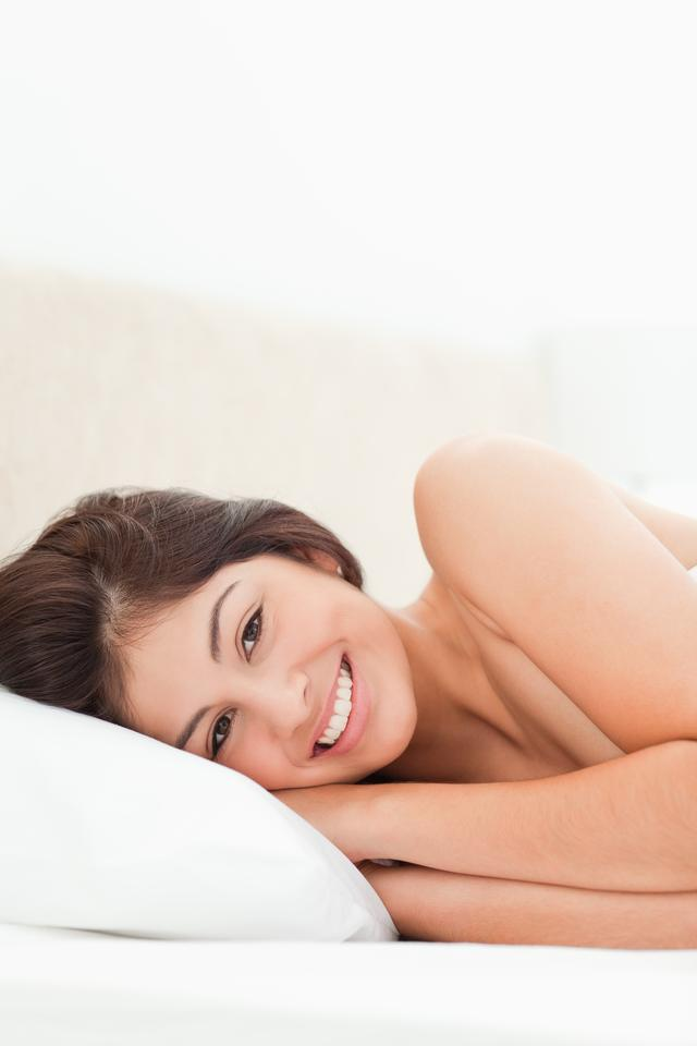 """A woman lying awake and smiling in bed"" stock image"