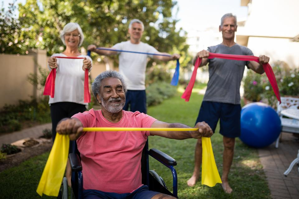 """""""Physically impaired senior man holding ribbon with friends"""" stock image"""