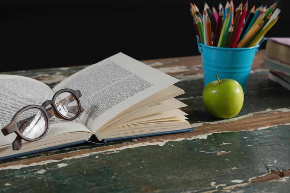 """""""Spectacles on open book with pen holder and apple"""" stock image"""
