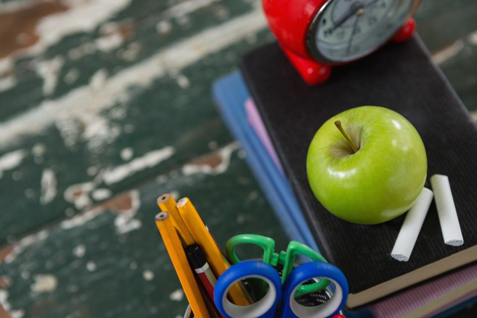 """""""Alarm clock, apple and chalk on stack of books with pen holder"""" stock image"""