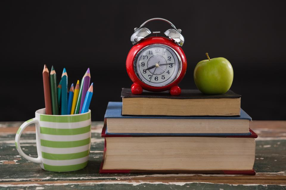 """""""Alarm clock and apple on stack of books with pen holder"""" stock image"""