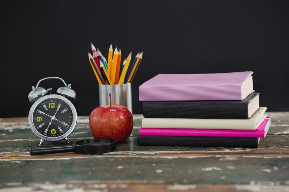 """""""Stack of books with alarm clock, apple, magnifying glass and pen holder"""" stock image"""