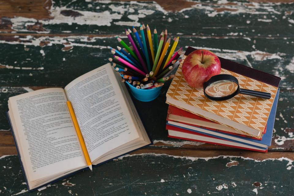 """""""Stack of books with apple, magnifying glass and pen holder"""" stock image"""