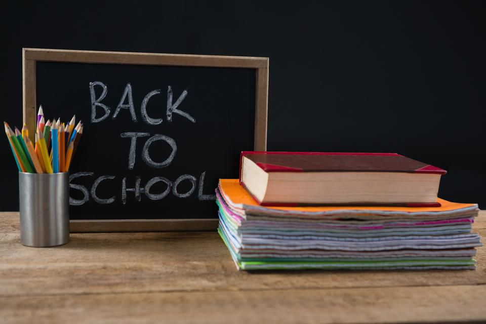 """""""Back to school text written on chalkboard with book stack and pen holder"""" stock image"""