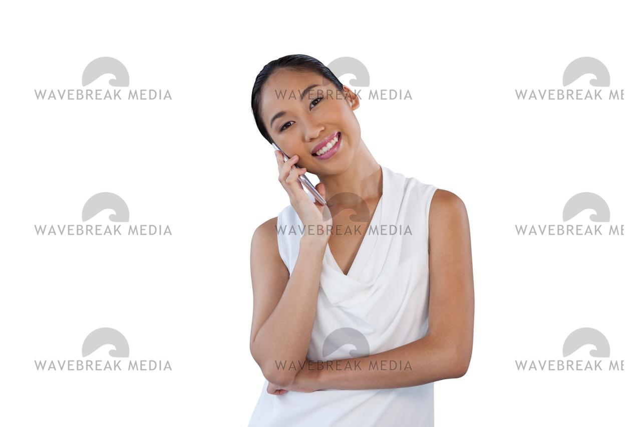 Happy Businesswoman With Head Cocked Talking On Mobile Phone