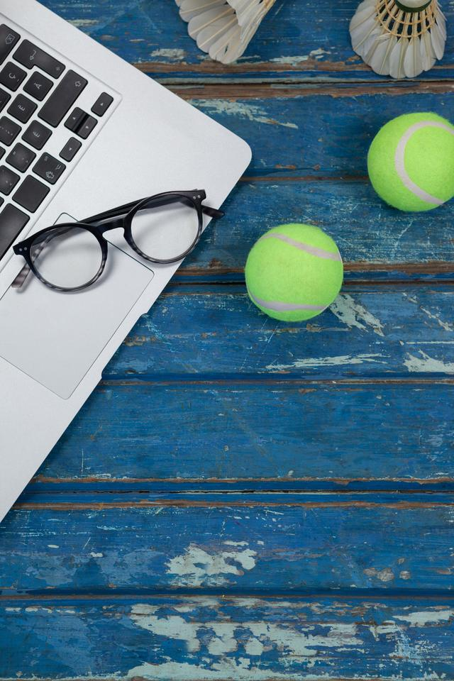 """Overhead view of laptop and eyeglasses with shuttlecocks by tennis balls"" stock image"
