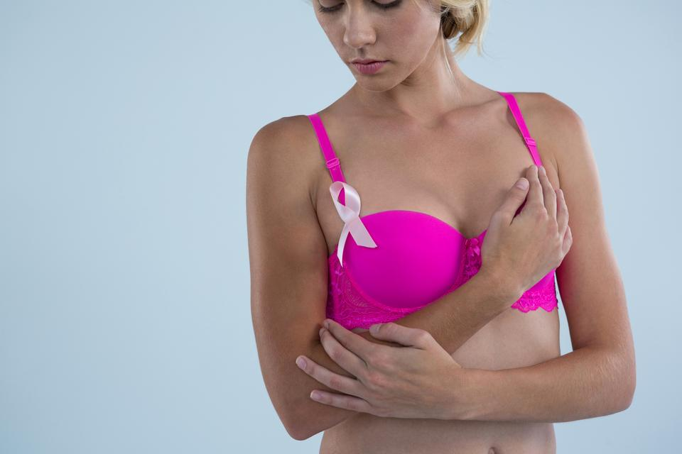 """Woman with Breast Cancer Awareness ribbon"" stock image"