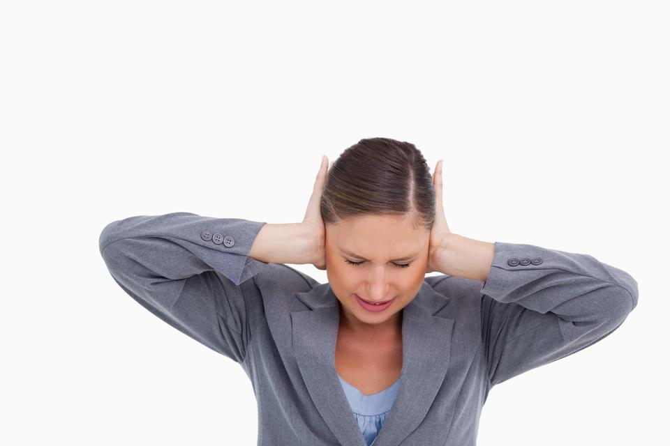 """Close up of irritated tradeswoman covering her ears"" stock image"