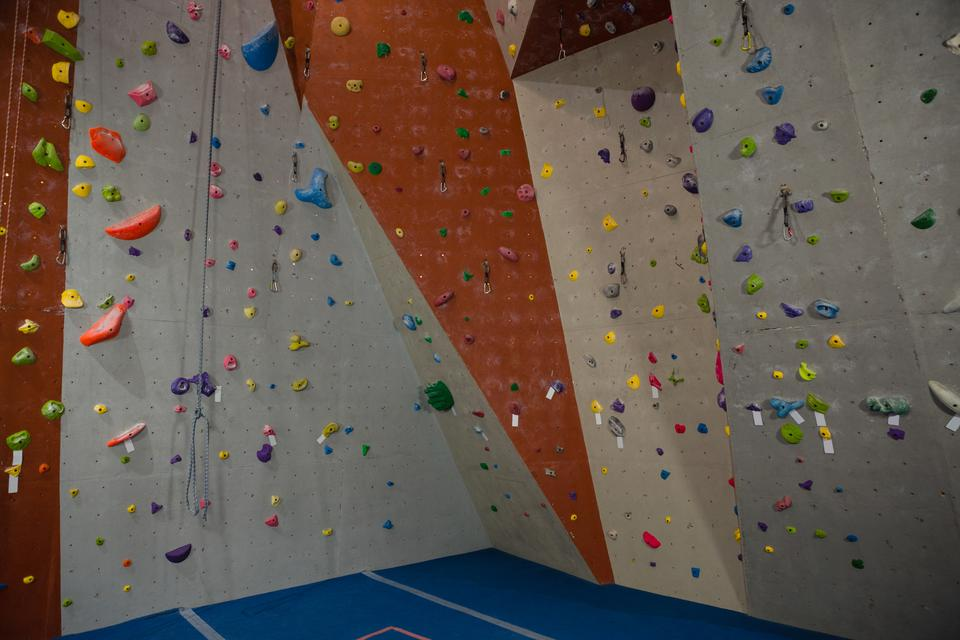 """Handgrips on climbing wall at gym"" stock image"