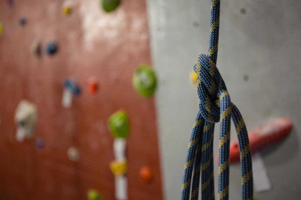 """Close up of rope against climbing wall at gym"" stock image"