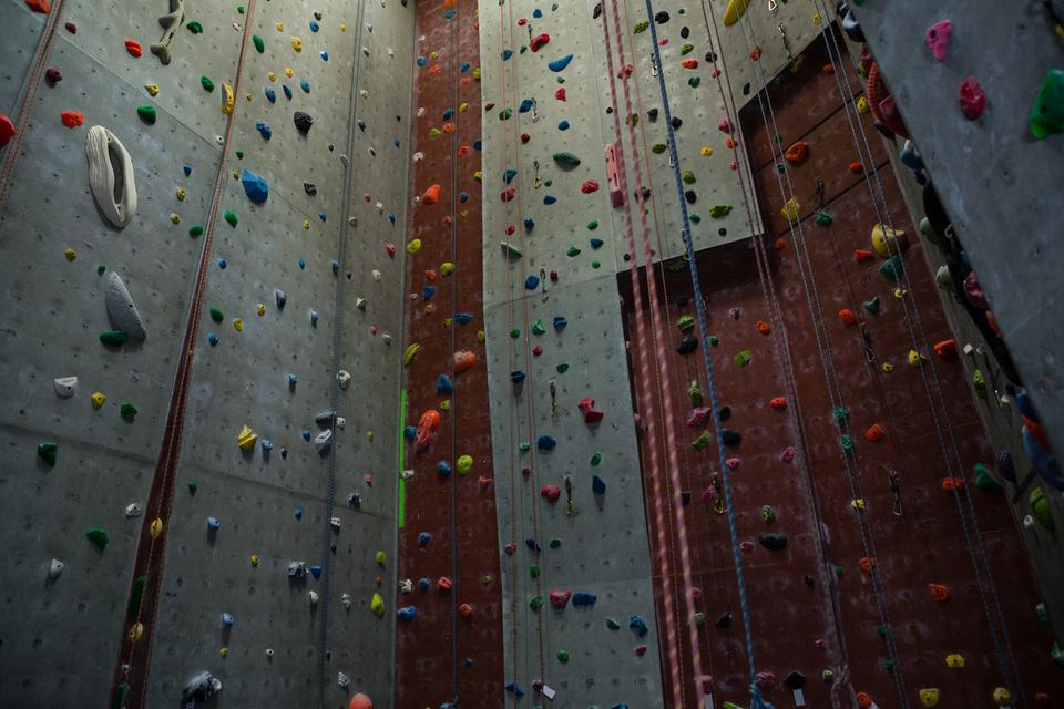 """Ropes hanging by climbing wall in gym"" stock image"