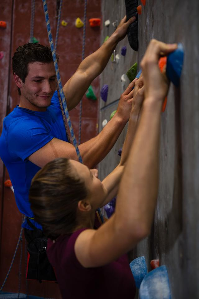 """""""Athletes climbing wall in health club"""" stock image"""