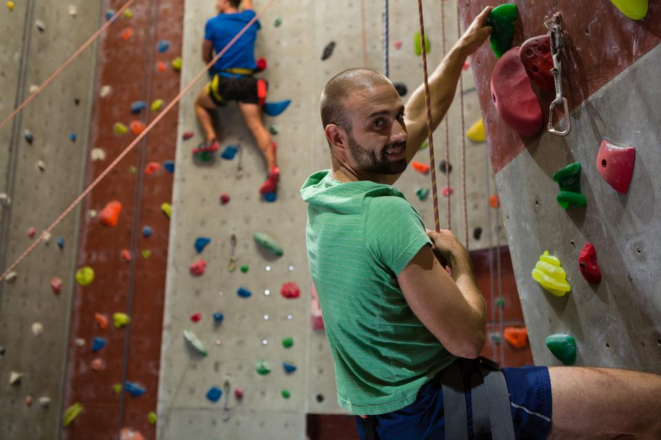 """""""Portrait of athlete climbing wall in health club"""" stock image"""