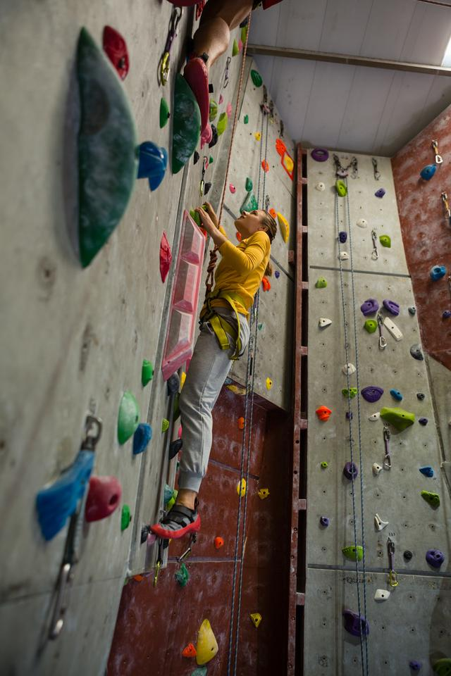 """""""Full length of female athlete rock climbing in club"""" stock image"""