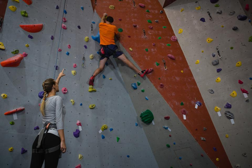 """""""Woman instructing athlete in climbing wall at health club"""" stock image"""