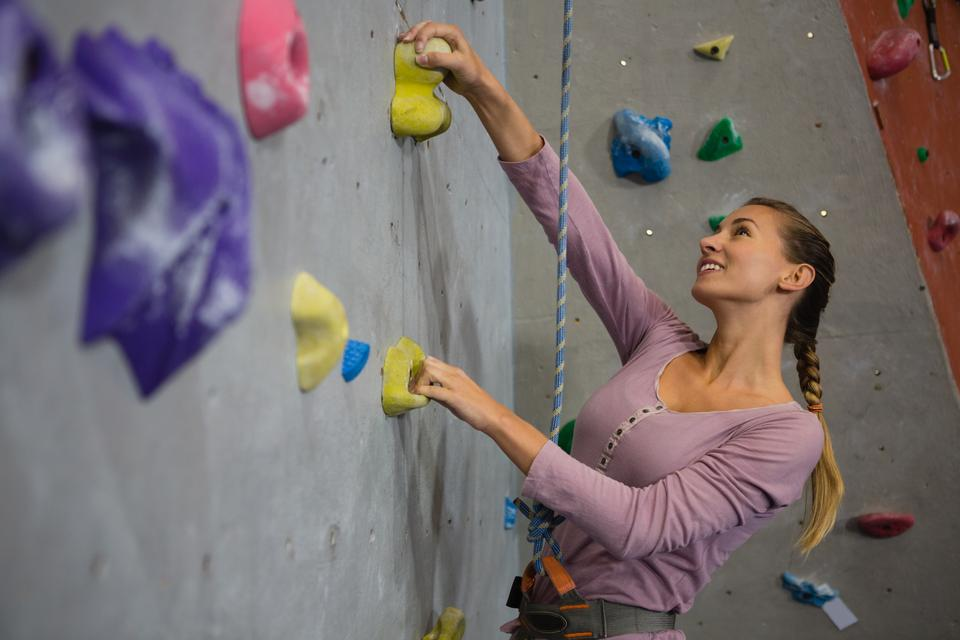 """""""Smiling athlete climbing wall in health club"""" stock image"""