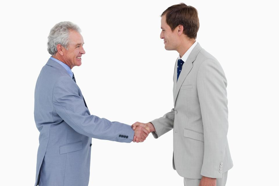 """""""Side view of tradesmen shaking hands"""" stock image"""