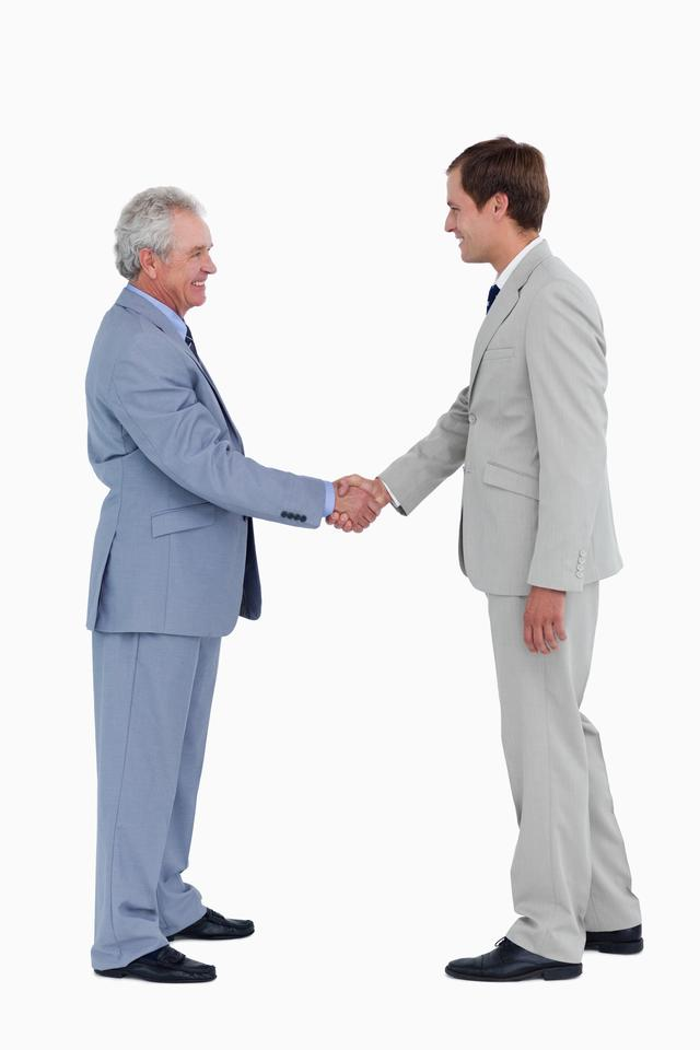 """""""Side view of smiling tradesmen shaking hands"""" stock image"""