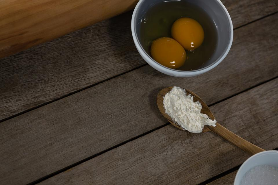 """""""Egg yolk and flour in spoon on a wooden table"""" stock image"""