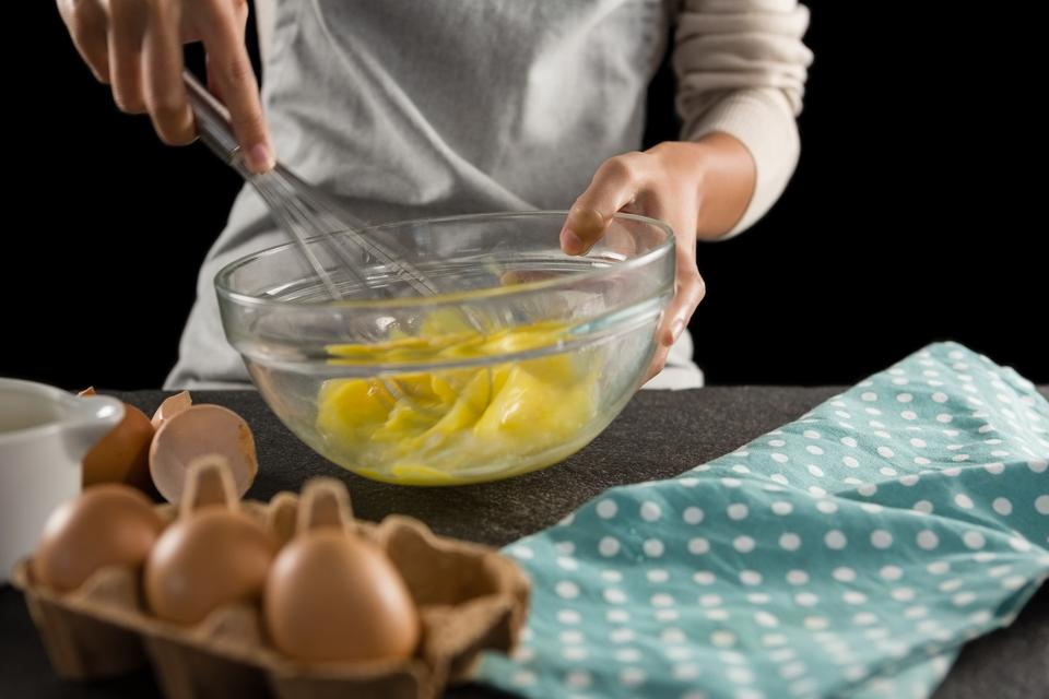 """Woman beating eggs with a whisk in a bowl"" stock image"