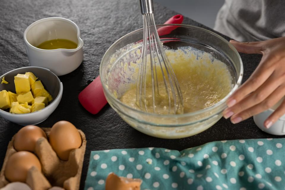 """Woman whisking batter of beaten eggs and milk in a bowl"" stock image"