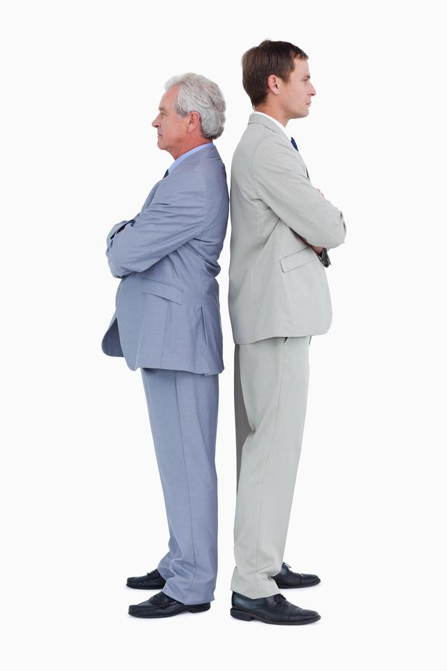 """""""Side view of serious tradesmen standing back-to-back"""" stock image"""