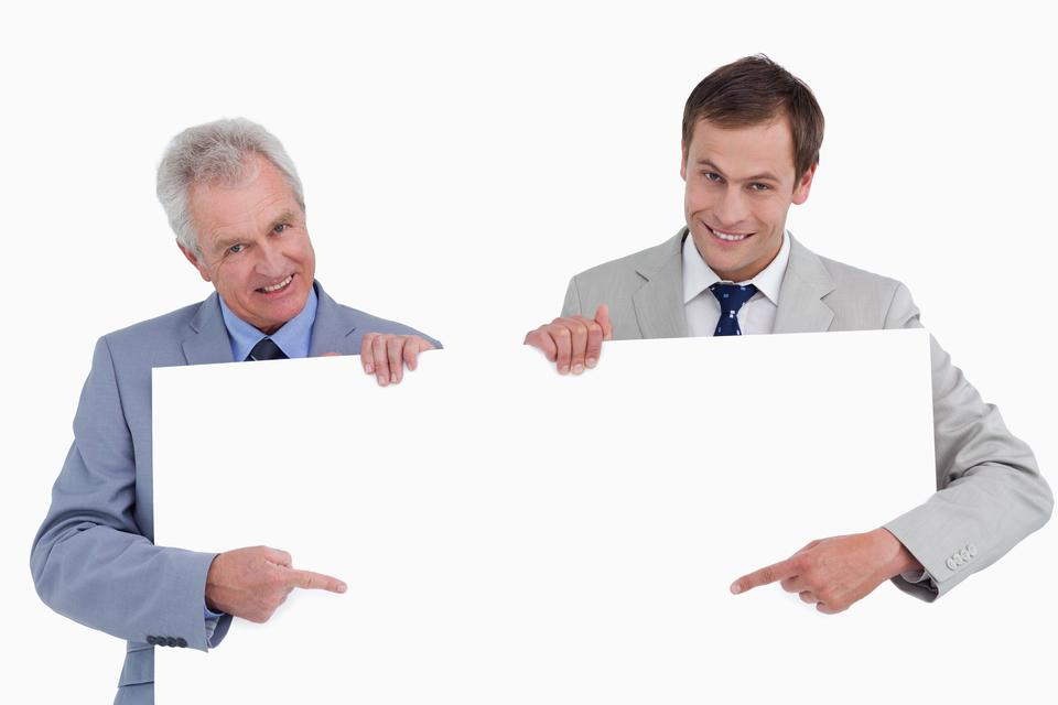 """""""Smiling tradesmen pointing at blank sign in their hands"""" stock image"""