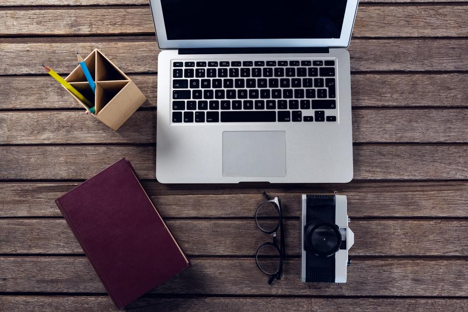 """""""Laptop, diary, spectacles, camera and pen holder on wooden table"""" stock image"""