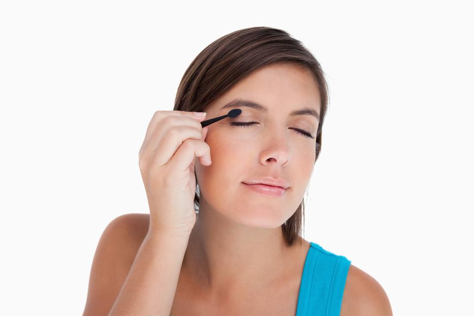 """Teenager applying eyeshadow in a concentrated way"" stock image"