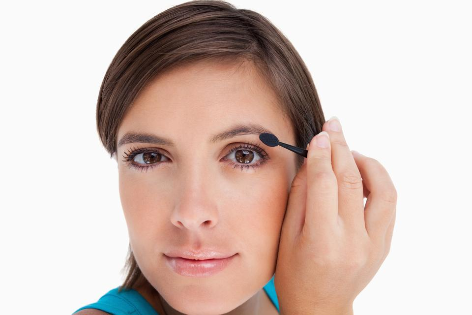 """""""Young woman looking at the camera putting eyeshadow on her eyelid"""" stock image"""