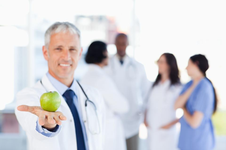 """Mature doctor holding a green apple"" stock image"