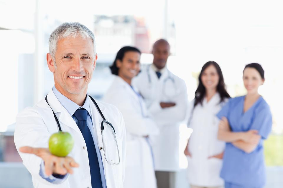 """Mature doctor holding an apple while his medical team is looking at him"" stock image"