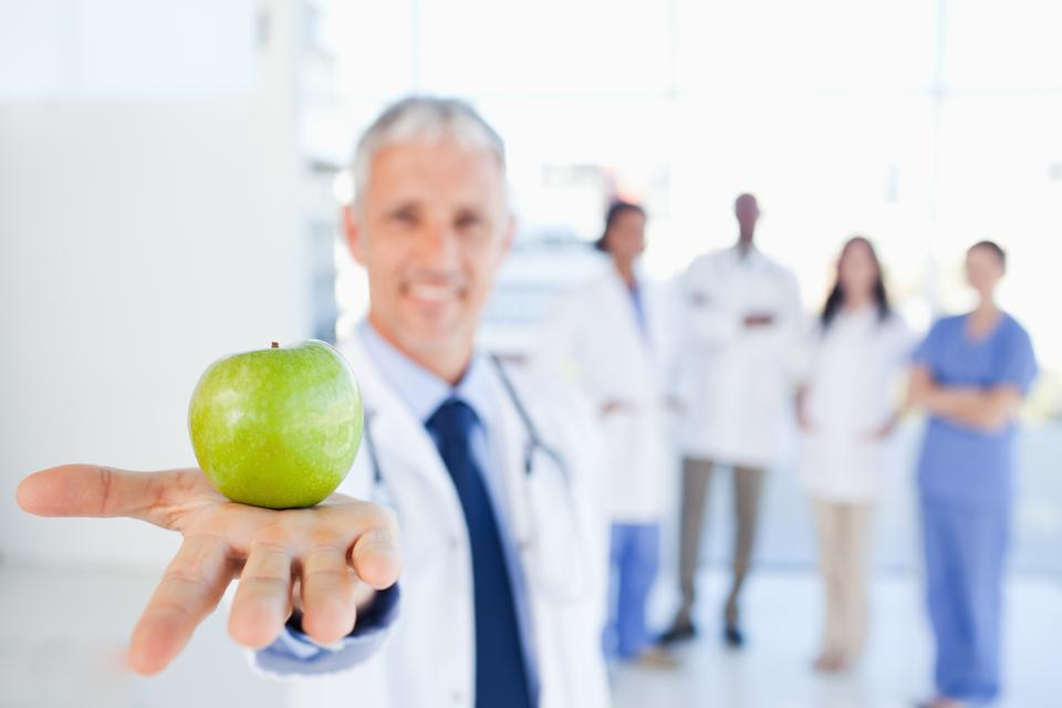 """Green apple held by a doctor with a team behind him"" stock image"