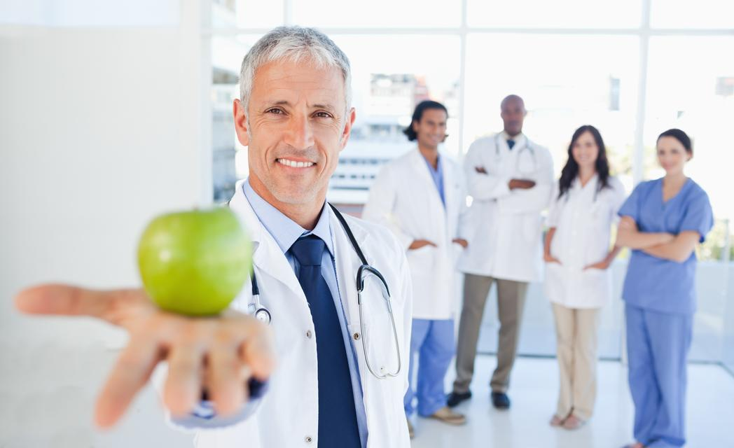 """Medical team in the background looking at a doctor who is holding a green apple"" stock image"